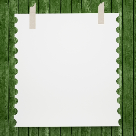 Notebook paper. White page pasted to a wooden wall, vintage background. photo