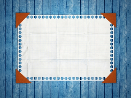 wooden insert: Notebook paper. Tattered squared white page pasted to a wooden, blue background. Stock Photo