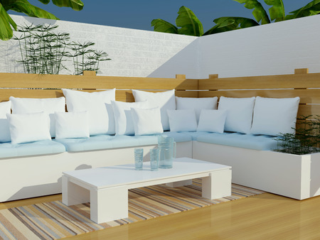 seating area: Outdoor patio seating area with big white sofa and table.
