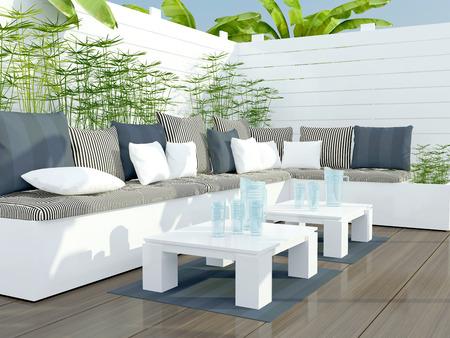 Buiten patio zithoek met grote witte bank en tafel.