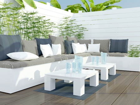 sofa furniture: Outdoor patio seating area with big white sofa and table.