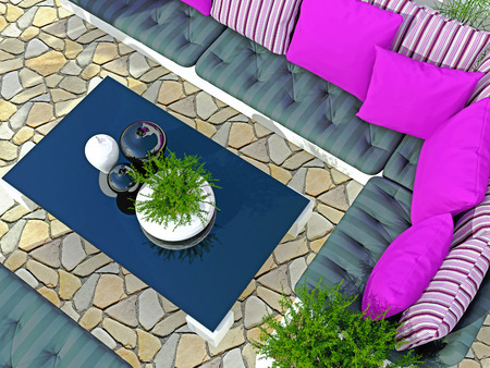 patio furniture: Outdoor patio seating area with big sofa and black table. Stock Photo