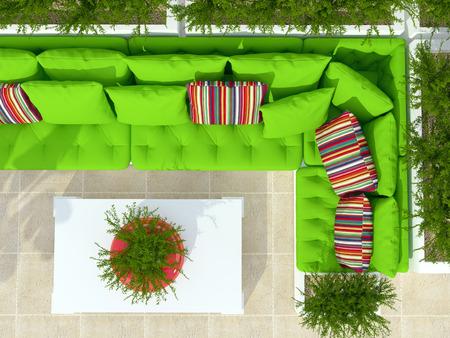Buiten patio zithoek met grote groene sofa, witte tafel en planten.