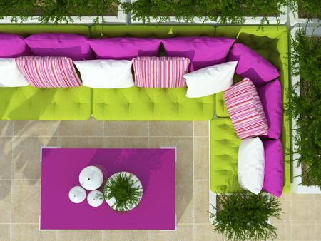 Buiten patio zithoek met grote groene bank, roze tafel en planten.