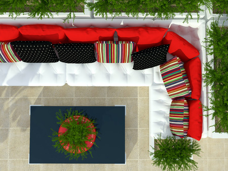 seating area: Outdoor patio seating area with big white sofa, red pillows and table.