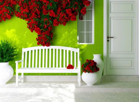 facade: Vista frontal de una puerta blanca de madera en una casa verde con ventana. Hermosas rosas rojas y un banco en el porche. Exterior de una casa.