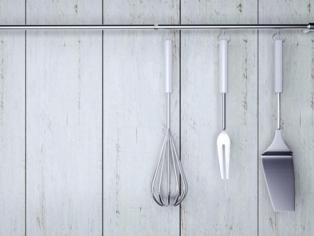 Kitchen cooking utensils. Steel spatulas, whisk in front of rustic white wooden wall. Stock Photo