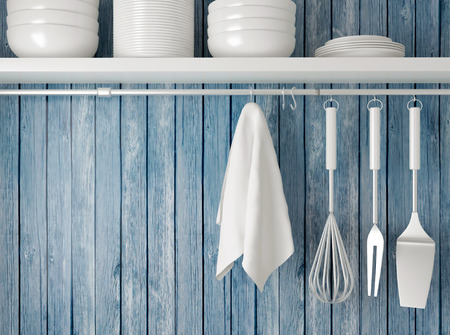 White plates on the shelf, kitchen cooking utensils. Steel spatulas, whisk and towel in front of rustic blue wooden wall.  Foto de archivo