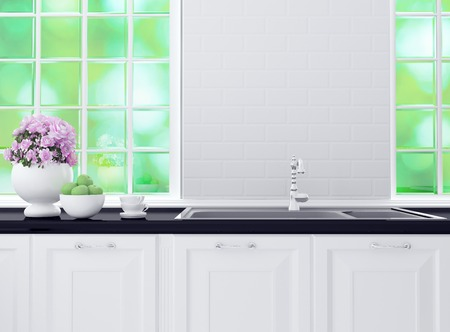 Kitchenware on the black marble worktop in front of big light window. White and black kitchen design.