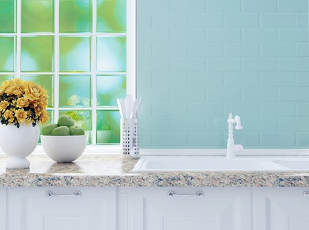 Kitchenware on the marble worktop in front of big light window. White kitchen design. Stock Photo