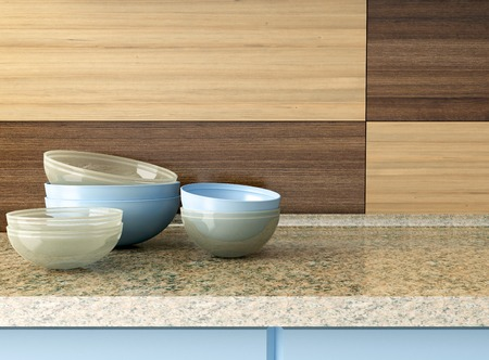 Ceramic and glass kitchenware on the marble worktop in front of modern wooden wall. photo