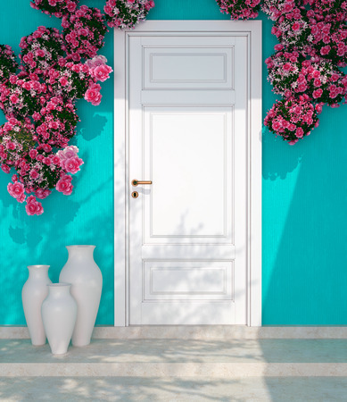 Beautiful roses and door in front of blue wall. Entrance of a house. photo