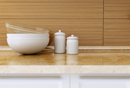 Ceramic and glass kitchenware on the marble worktop in front of modern wooden wall. White kitchen design. photo
