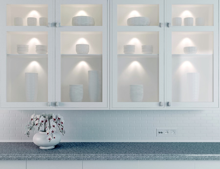 White kitchen design, orchid on the marble worktop. Ceramic tableware in the buffet.