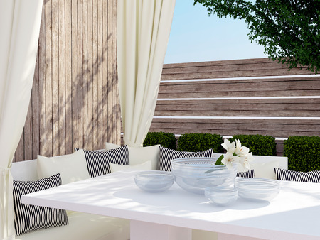 upmarket: Outdoor patio seating area with big sofa, black and white pillows and table. Stock Photo