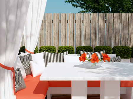 patio: Outdoor patio seating area. Big red sofa, black and white pillows. Beautiful flowers on the table.