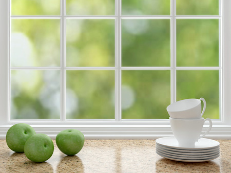 windows: Cups and apples on the marble worktop in front of big window.