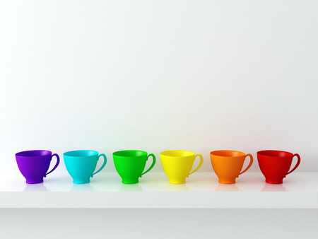 Rainbow ceramic cups on the shelf in front of white wall. Reklamní fotografie