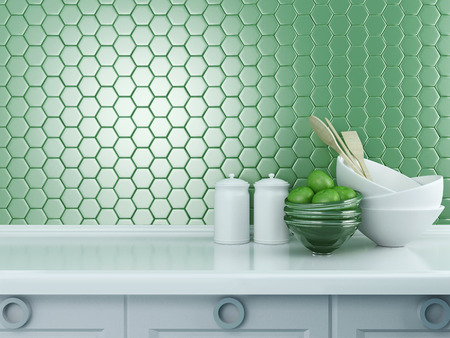 worktop: Kitchen utensils on the white worktop. Ceramic and glass kitchenware in front of modern green tile. Stock Photo