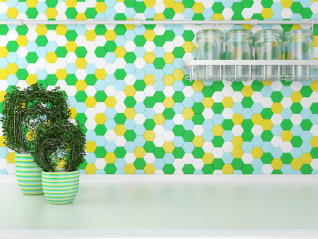 worktop: Green plants on the white worktop. Glass kitchenware on the cupboard. Stock Photo