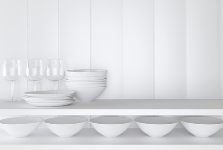White ceramic kitchenware and wineglasses on the shelf in front of white wall. Reklamní fotografie
