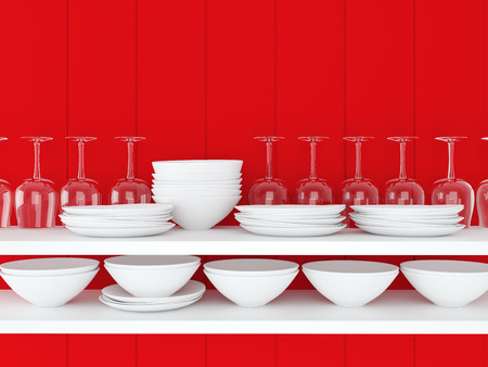 White ceramic kitchenware and wineglasses on the shelf in front of wooden red wall.