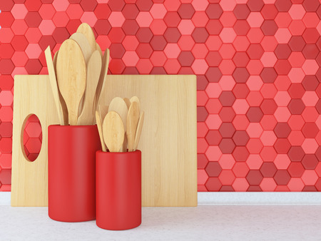 Wooden utensils on the white worktop in front of red tile wall.