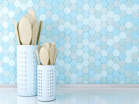 Wooden utensils on the white worktop in front of blue tile wall.