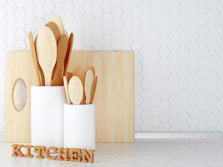 worktop: Wooden utensils on the white worktop in front of white tile wall. Stock Photo