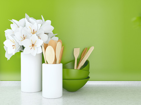 Wooden utensils and flowers on the white marble worktop in front of green wall.
