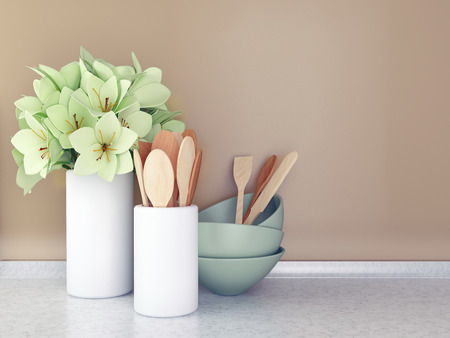 kitchen tiles: Wooden utensils and flowers on the white marble worktop in front of brown wall. Stock Photo