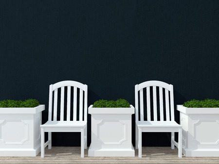 Outdoor patio seating area with white wooden furniture, black wall.