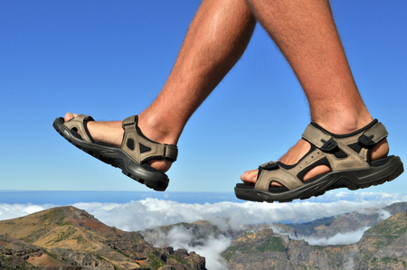 Man walking above the clouds in sports shoes.
