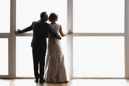 adult bride and groom hug and stand near a large window with their backs to the viewer Stock fotó
