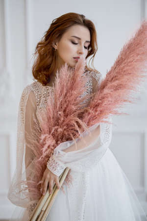 red-haired woman in a bright room with pink feathers