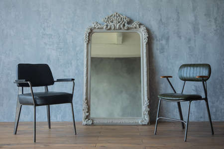 two black chairs and more mirror on the background of a gray wall Stock Photo