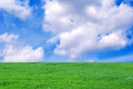 The Clouds on turn blue the sky. The Green meadow. Stock Photo