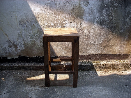 Wooden old chair with Old concrete wall. Textured background photo