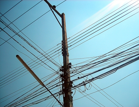 Chaotic wire on electric posts and blue sky background photo