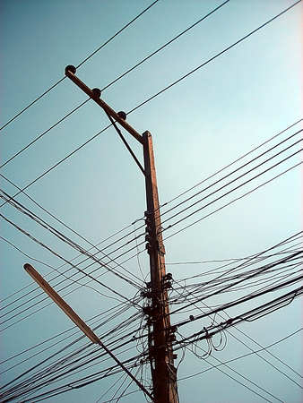 chaotic: Chaotic wire on electric posts and blue sky background