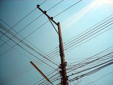 voltage gray: Chaotic wire on electric posts and blue sky background
