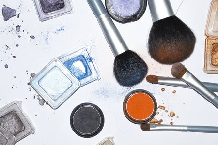 photo of makeup accessories scattered all over the table