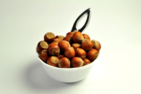 hazelnuts in a white bowl with nutcracker