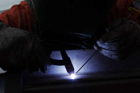 welds: welder welds the metal tungsten inert gas
