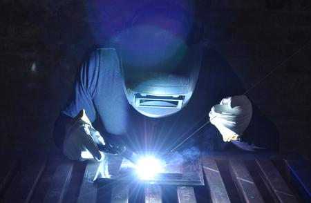 spawacz spawa metal metodą TIG na czarnym tle Zdjęcie Seryjne