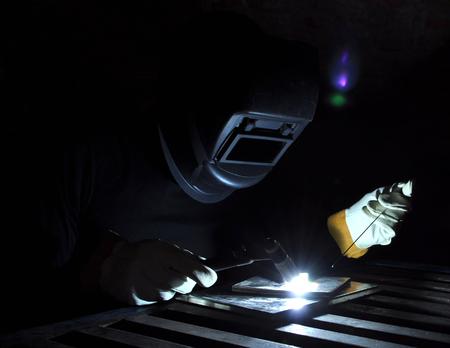 welder welds metal using tig with black background