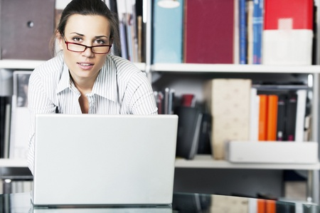 Young women with glasses works on a laptop in a modern office photo