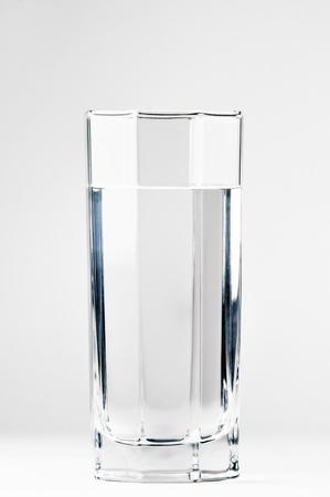 vaso con agua: Con un vaso de agua sobre un fondo blanco Foto de archivo