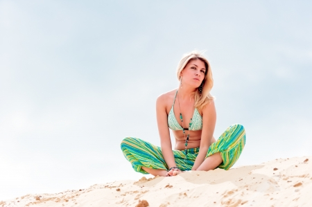 A young woman is concentrated and sits on the sand. photo