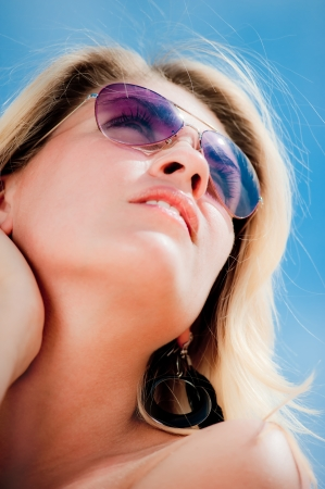 Portrait of a young woman wearing sunglasses, looking to the sky.